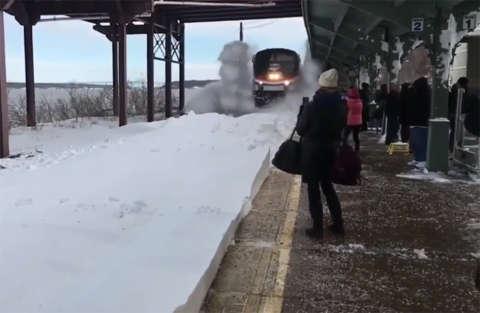 Il treno all'entrata in stazione solleva un'ondata di neve